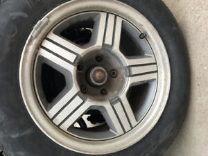 4 - S10 rims with two tires and GMC center caps