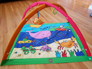 Baby play mat with rings and hanging toy.