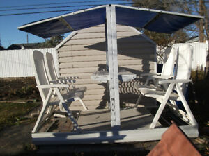 White glider swing with table. Chairs recline and have pads,  Re