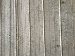 Speckled grey sheets of steel siding/roofing for sale.