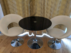 Stylish glass dining table with 2 swivel chairs