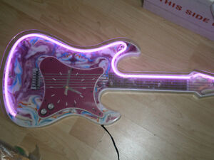 pink and white neon guitar with clock
