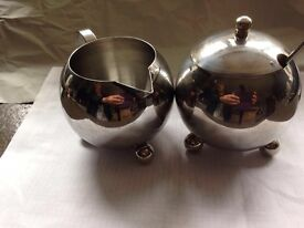 Stainless steel milk pourer and sugar pot.