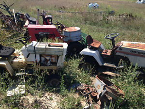 Three old lawn mowers one rototiller