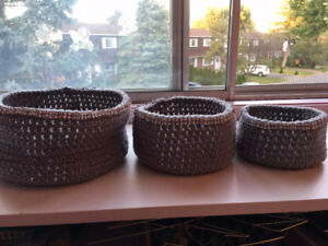 Set of three stackable hand-made crochet baskets.