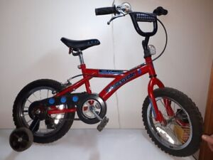 Red pedal bike with take-off training wheels.