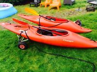 2 kayaks with paddles, trolleys and skirts.