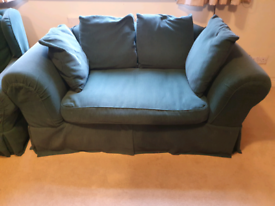 Two-seater sofa with removable covers and loose cushioned back
