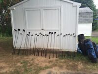 Lots of golf clubs and 2 bags