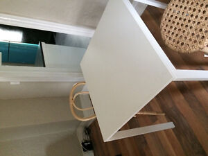 Small white table and two wicker chairs