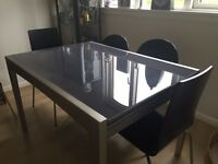 Extendable glass and metal dinning table & 4 matching black dinning chairs