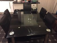Black and silver glass dining table with 6 faux leather chairs