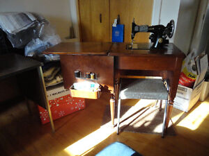 Vintage SINGER electric sewing machine in cabinet, with bench