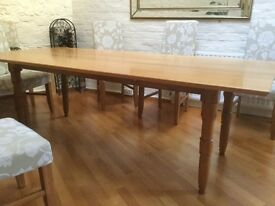 solid oak bespoke dining table with turned legs and a bevelled edged top