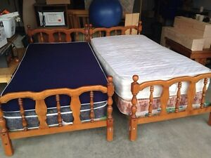 Two single bed frames and four mattresses