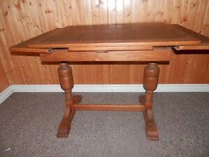 WOOD TABLE HAS SOLID WOOD BASE WITH WOOD AND VENEER TOP