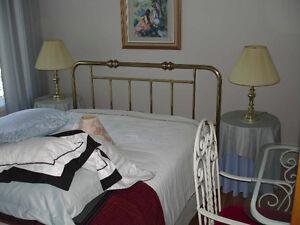 Tête de lit de laiton, lampes et tables en bois