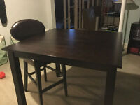 Dark wood high-top kitchen table with 4 brown leather bar chairs