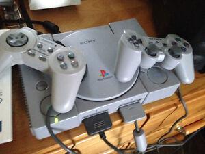 Console PlayStation 1 avec 2 manettes et un jeux.