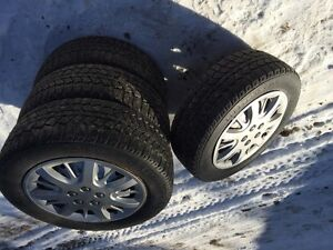 Four snow tires with rims and hub caps