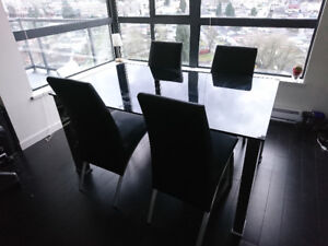 Beautiful black glass dining table with 4 matching black chairs.