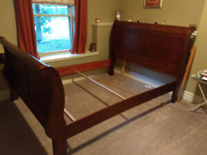 Cherry color queen size sleigh bed.