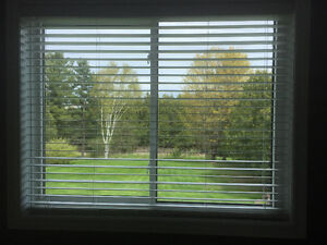 Two white faux wood window blinds