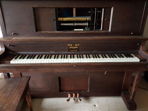 Antique Player piano with a hundred player rolls plus cabinets..