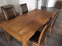 Beautifully crafted extendable solid wood table with 4 high back leather bound chairs