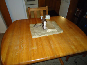 Heavy, solid oak kitchen table with four matching chairs