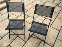 Two fold up black chairs