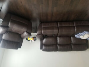 Beautiful leather doubled reclining couch and chair.