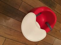 Red Bumbo baby seat with straps and tray