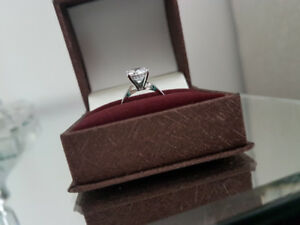 A beautiful engagement ring in 14 karat white gold diamonelle.