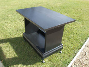 Black wooden craft table with wheels.