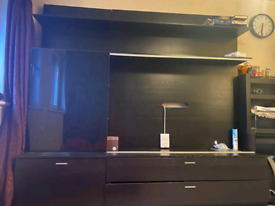 Full wall shelving and tv unit with sliding glass panel