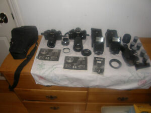 2 Canon A1  35mm Cameras with lenses and flash