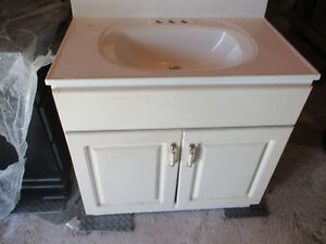 White bathroom sink and vanity and white laundry cupboard
