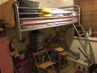 Tubular steel high sleeper bed frame with desk below.