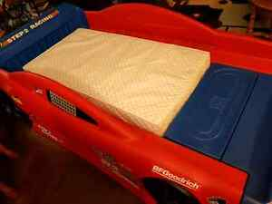 Children's twin size race car bed with toddler/crib mattress.