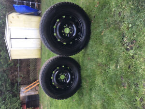 A pair of rims and winter tires for a Chevy