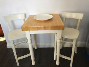 Solid wood butcher block table/island with bar stools.