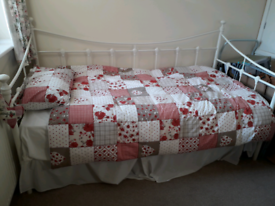 White single day bed with mattress.