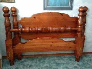 Pine queen size bed with railings.