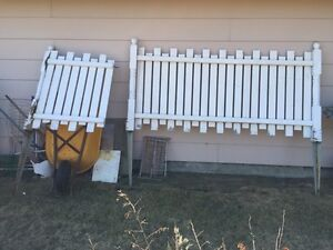 Solid painted wood fence with latch door