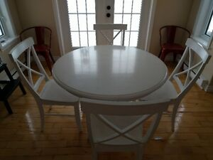 White solid wood table and four chairs