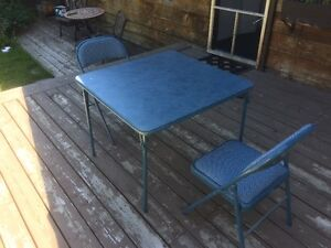 Padded card table and two folding chairs.