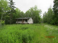 Unfinished cottage on 2.7 acres in area of great beaches