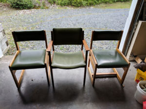 Three vintage and authentic vinyl and solid wood office chairs.