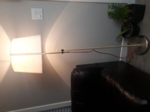 Floor standing lamp with off white fabric shade.